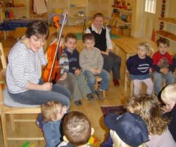 A parent shows the children her viola